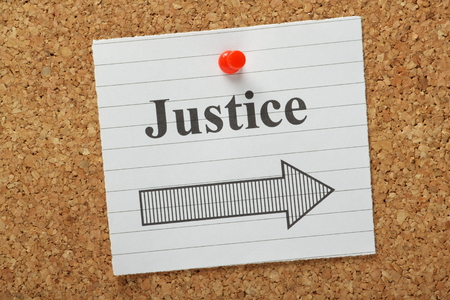 recompense: The word Justice above an arrow pointing in the right direction on a lined paper note pinned to a cork notice board