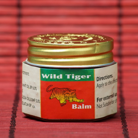 ointment: London, England - October 1st, 2014: A jar of Wild Tiger Balm red ointment, a topical analgesic made from herbal ingredients. It is estimated that 20 million jars are sold every year in 70 countries.