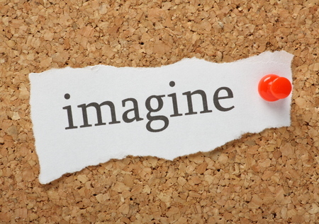 The word imagine typed on a scrap of plain white paper and pinned to a cork notice board photo