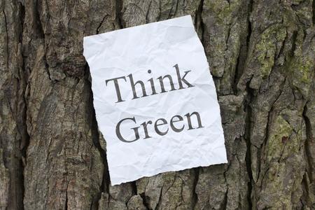 arbol de problemas: La frase Think Green en un aviso papel normal pegado a la corteza de un árbol como un mensaje a tener en cuenta el impacto ambiental. Foto de archivo