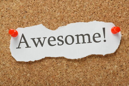 The word Awesome! typed on a scrap of paper and pinned to a cork notice board photo