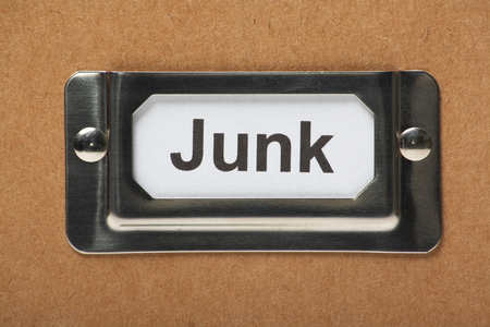 prioritize: Drawer label in a holder on a cardboard box with the word Junk typed onto the index card