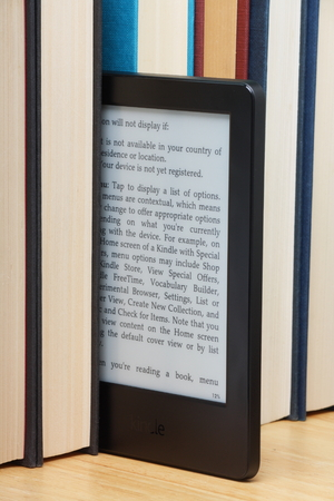 kindle: Bracknell, England - October 20th, 2014: A Kindle Touch Reader standing out from a row of old hardback books. Manufactured by Amazon the device is a portable library of books and other publications