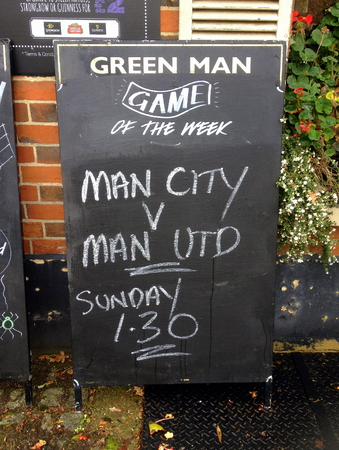 premiership: Bracknell, United Kingdom - October 31, 2014: Blackboard sign outside The Green Man Public House advertising TV coverage of the Manchester United and Manchester City Premier League Football match Editorial