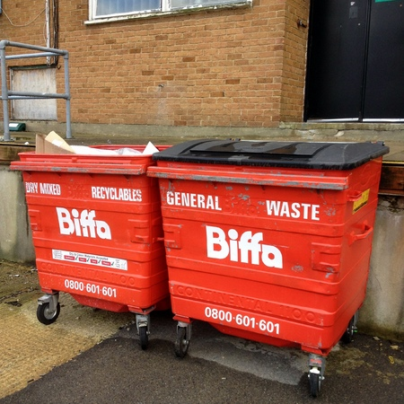 waste management: Bracknell, United Kingdom - November 1st, 2014: Two red Biffa wheelie bins awaiting collection. Biffa is the UKs leading waste management business for collection, treatment and recycling Editorial