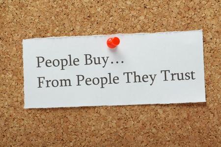 Die Phrase Menschen kaufen von Menschen, denen sie vertrauen auf einem Kork Brett als Konzept für Unternehmen, um Kunden Vertrauen und Loyalität zu ihrem Produkt oder eine Dienstleistung zu bauen.