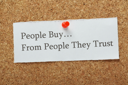 trust people: The phrase People Buy From People They Trust on a cork notice board as a concept for businesses to build customer trust and loyalty to their product or service.
