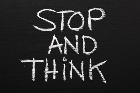 take time out: The phrase Stop and Think written on a blackboard as a reminder to take time out and work through our options before taking action