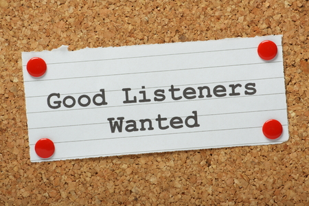 The phrase Good Listeners Wanted typed on a piece of paper and pinned to a cork notice board