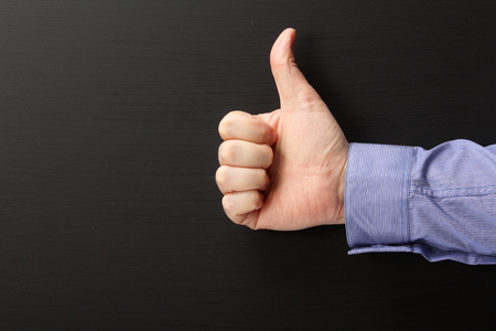 acknowledge: Male hand wearing a business shirt giving the thumbs up sign against a blank blackboard with copy space