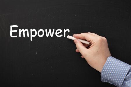 autonomia: Escribir la palabra Empower en una pizarra