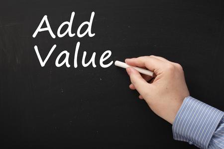 ajouter: Main Homme vêtu d'une chemise d'affaires écrit la phrase Ajouter une valeur dans un tableau noir.