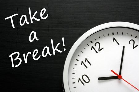 Der Ausdruck Take A Break auf einer Tafel neben einem modernen Büro-Uhr. Eine Erinnerung, Zeit in Ihrem Terminkalender zu finden um sich zu entspannen Standard-Bild - 33717544
