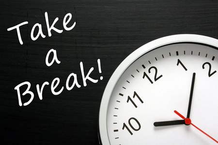 The phrase Take A Break written on a blackboard next to a modern office clock. A reminder to find time in your busy schedule to relax
