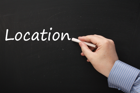 the place is important: Male hand in a business shirt writing the word Location on a blackboard using white chalk. Location is often a factor when buying a home or providing a service or business Stock Photo
