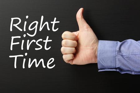 best practices: The phrase Right First Time on a blackboard with a male hand in a business shirt giving the thumbs up sign. Right First Time is a term used in Quality Control Improvement