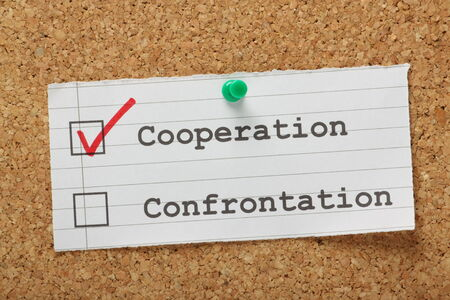 best practices: Tick boxes for cooperation versus confrontation on a cork notice board, with a red tick for the right choice in the cooperation box