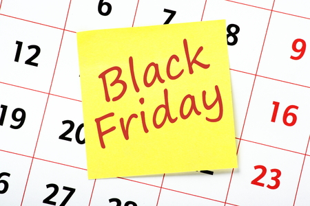prompt: Black Friday reminder written on a yellow sticky note attached to a wall calendar Stock Photo