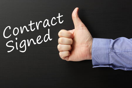 formalities: Male hand wearing a business shirt giving the Thumbs Up gesture to the words Contract Signed written on a blackboard