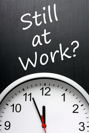 burning time: The phrase Still at Work? on a blackboard above a clock with the time at almost midnight or twelve oclock