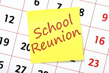 calendario escolar: Recordatorio de una reunión de la escuela por escrito en una nota adhesiva amarilla y unido a un calendario de pared