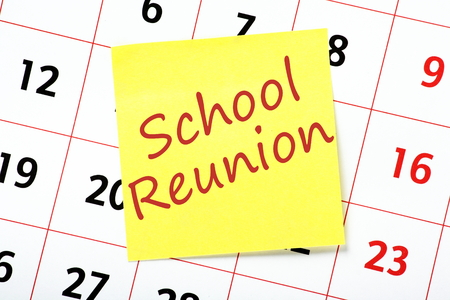 formative: Reminder of a School Reunion written on a yellow sticky note and attached to a wall calendar Stock Photo