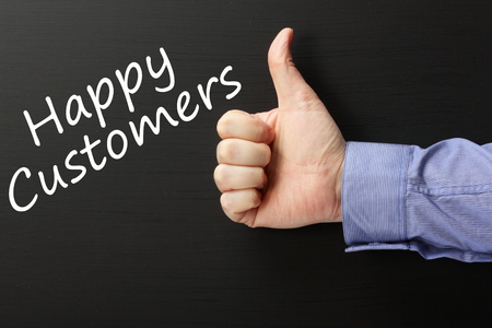 The phrase Happy Customers written on a blackboard with a male hand wearing a business shirt giving the Thumbs Up gesture