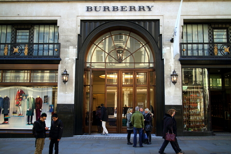 street name sign: London, England - January 24, 2015: People in front of and entering the Burberry flagship store in Regent Street, London. The brand was founded by Thomas Burberry in 1856