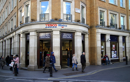 premises: London, England - January 24, 2015: Pedestrians pass by the Tesco Metro store near Covent Garden in London, England. Tesco was founded in 1919 by Jack Cohen as a market stall in London\\\\
