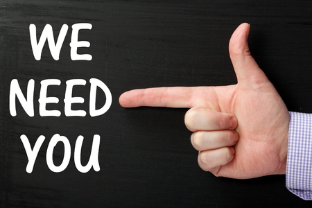 point of demand: Male hand wearing a business shirt pointing at the phrase We Need You written on a blackboard