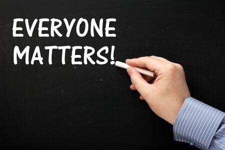 human representation: Male hand wearing a business shirt writing the phrase Everyone Matters on a blackboard using white chalk