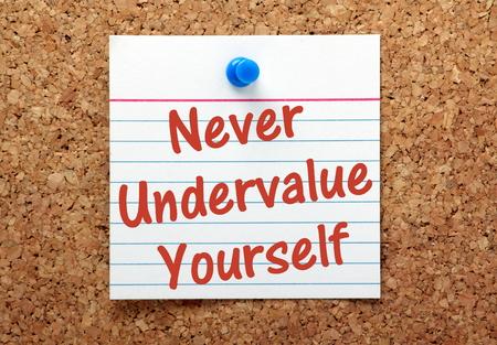 nunca: La frase Nunca infravalorar usted mismo escrito en una tarjeta y cubri� a un tabl�n de corcho como un recordatorio Foto de archivo