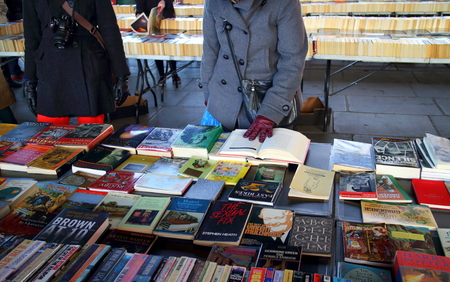 southbank: London, England - January 24, 2015: People browsing the books for sale at the Southbank Centre Book Market in London, England. Located beneath the Waterloo Bridge the market is open all year round.