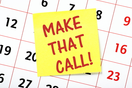 important phone call: The phrase Make That Call written on a yellow sticky note and on a wall calendar