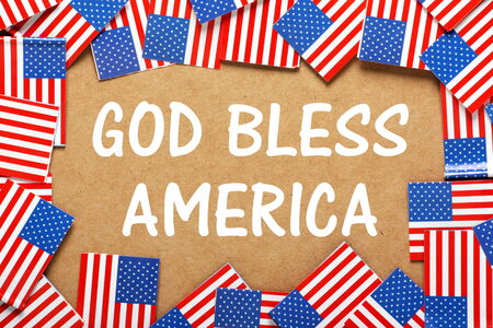 The phrase God Bless America in white text on a brown card background with a border of miniature flags of the United States of America Imagens