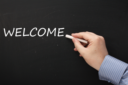 invited: Male hand wearing a business shirt writing the word Welcome on a blackboard using a stick of white chalk Stock Photo