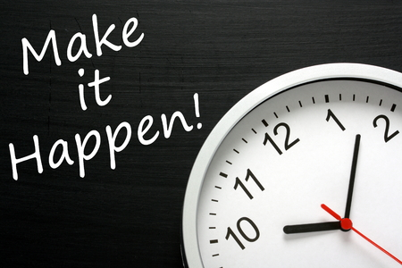 The phrase Make It Happen written on a blackboard next to a modern clock to emphasize the deadline