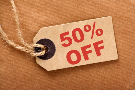 an announcement message: Fifty percent off announcement message in red text on a brown paper price tag and wrapping paper with string