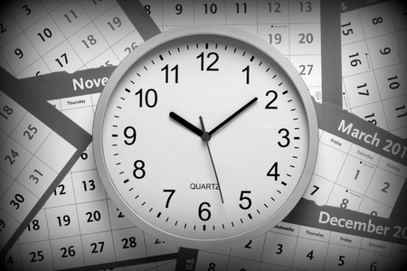 scattered: A black and white image of a modern office clock on a background of pages torn from a wall calendar. A vignette has been added for effect.