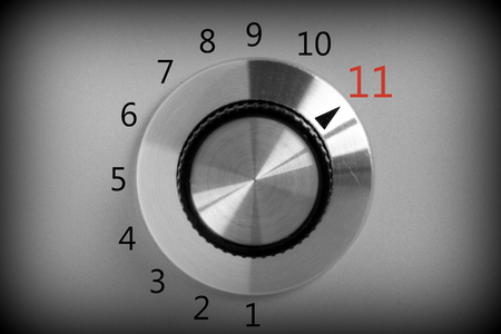 Black and white image of a volume or power control switch on a metal background that goes all the way up to the number eleven.