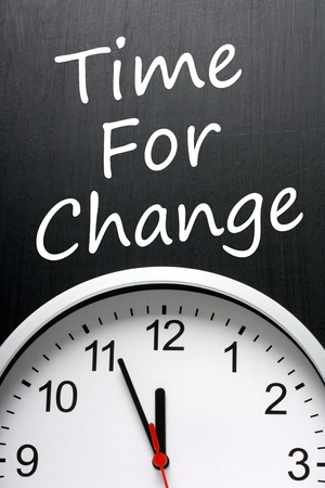 The phrase Time For Change written on a blackboard above a modern clock with the time at almost midnight or high noon