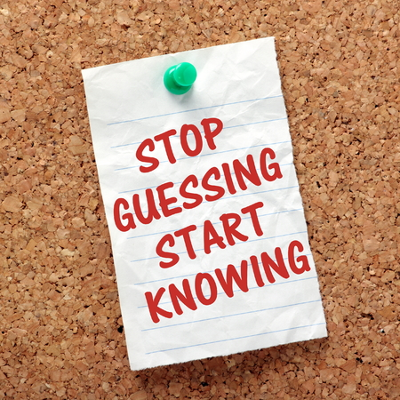 The phrase Stop Guessing Start Knowing on a piece of paper pinned to a cork notice board as a reminder to establish the facts Stock Photo