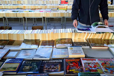 southbank: London, England - January 24, 2015: Person browsing the books for sale at the Southbank Centre Book Market in London, England. Located beneath the Waterloo Bridge the market is open all year round. Editorial