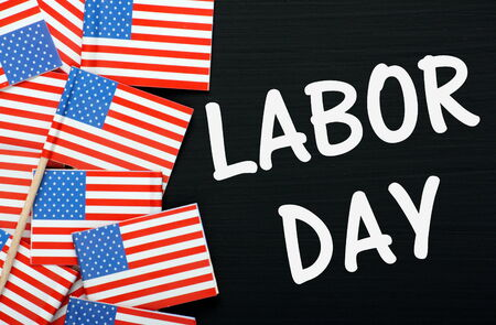 phrase: The phrase Labor Day on a blackboard alongside miniature flags of the United States of America