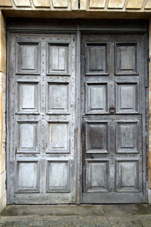 weather beaten: A pair of closed, old wooden doors at an outside entrance to a stone building