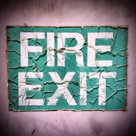 fire exit sign: A wrinkled and damaged Fire Exit sign stuck to an outside door. Creative filters and textures have been added for effect.
