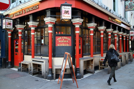 notable: London, England - February 17, 2015: A pedestrian passes by The Coach & Horses Pub in Soho, London on February 17th, 2015. The pub is notable as a regular haunt of journalists and Soho characters