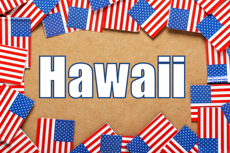 hawaii flag: Miniature flags of the United States of America form a border on brown card around the name of the state of Hawaii Stock Photo