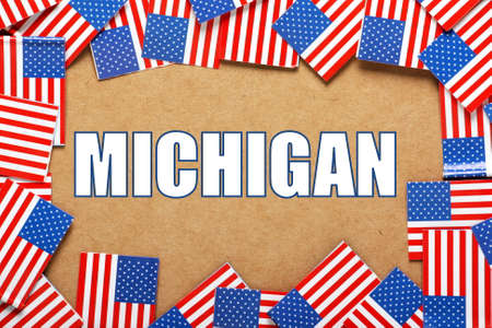 michigan flag: Miniature flags of the United States of America form a border on brown card around the name of the state of Michigan