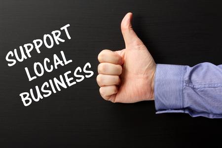 apoyo familiar: Mano de hombre vistiendo una camisa de negocios que el gesto Pulgar hacia arriba a la frase de apoyo empresarial local escrito en una pizarra